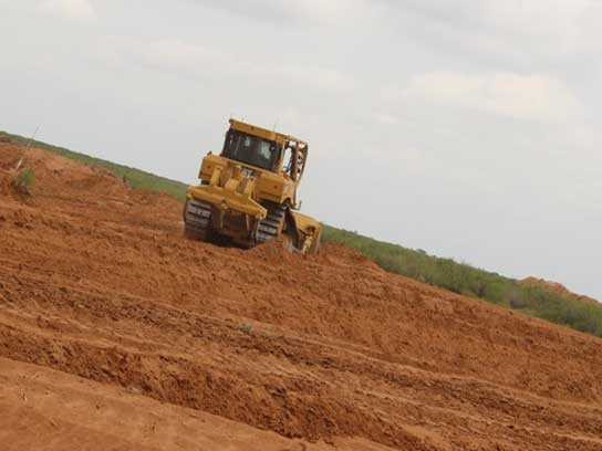 Large yellow heavy machinery with treads in a large dirt field.