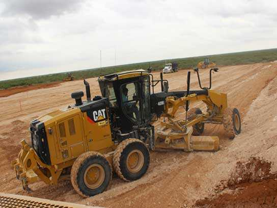 A large yellow tractor working hard in a dirt field.