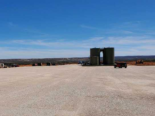 Oilfield site with white dirt, two very large barrels, and a truck.