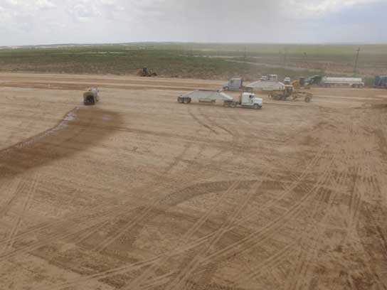 Large dirt field with lots of 18 wheelers and tire tracks.