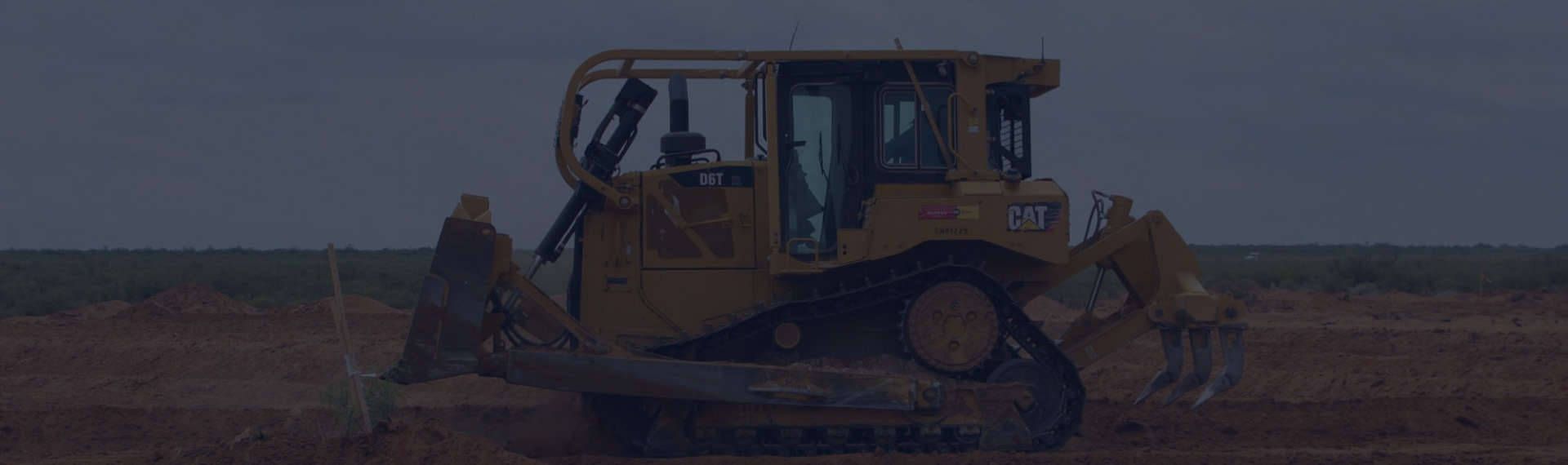 Piece of yellow Cat branded heavy machinery digging in the dirt.